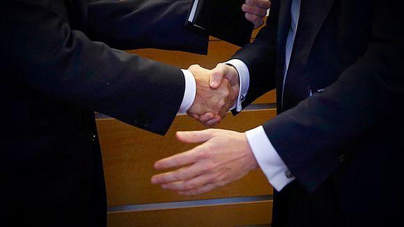 Miehet kättelevät