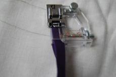 Le pied à biais permet de poser du biais sans épingles, sans surfilage ! Il est adaptable à la largeur du biais utilisé grâce à une petite molette à l'avant. La vis arrière permet de déplacer légèrement le pied pour placer  l'aiguille au mieux.