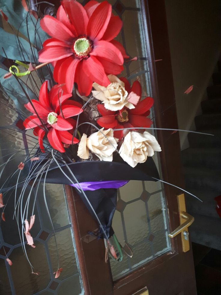 Some old fake flowers put into a witches hat to hang on the door.