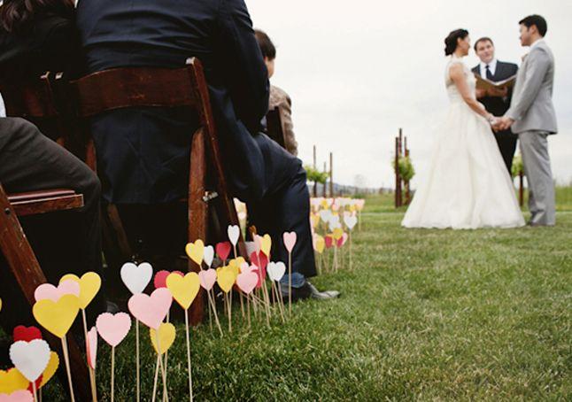 Une bordure du coeurs en papier pour cérémonie en extérieur. Quelques pics à brochettes ou petits tuteurs, une grosse perforatrice en forme de coeur, de la colle chaude ou du double face et hop, le tour est joué !