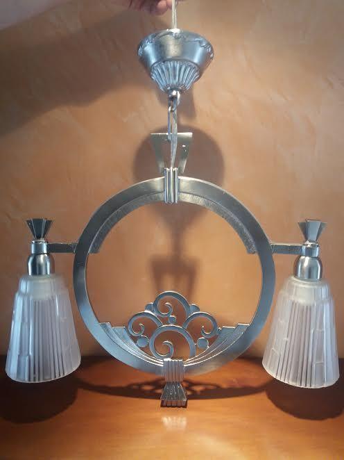 Frans jaren 1930 deco kroonluchter, met metalen frame en 2 lampjes met matglas tinten. Grootte: afstand tussen campanula tinten as 40 cm, hoogte 50 cm. Elektrische systeem gereviseerd. Geen schade, perfect intact.
