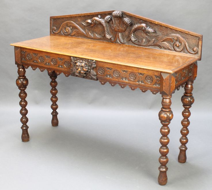 """Lot 968, A Victorian carved oak hall table, the raised back with Prince of Wales feathers, fitted 2 short drawers to the front and raised on ring turned supports 42""""h x 54""""w x 19 1/2""""d est £100-200"""