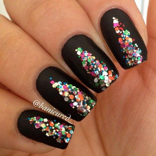 Nail polish and sequins Christmas nail art combination. By filling your nails with a black polish background the colorful sequins you place on top is given more highlight and you can even use a variety colors for effect.