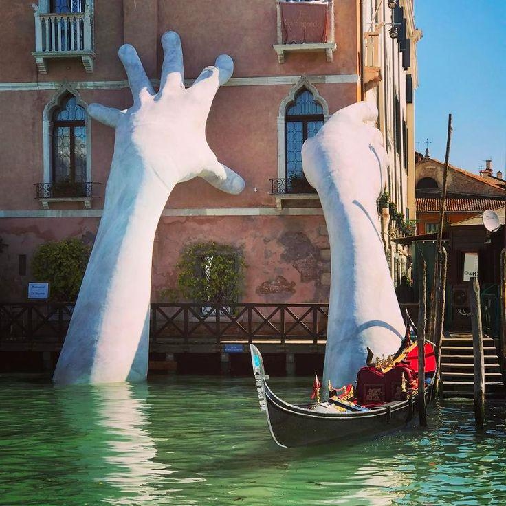 """Des mains géantes et monumentales - 8 à 9 mètres de haut - sortent de l'eau à Venise, sur le grand canal, pour soutenir des immeubles, dont l'hôtel """"Ca' Sagado"""", afin d'alerter sur le changement climatique. Elles sont l'oeuvre de l'artiste italien Lorenzo Quinn. Une exposition a lieu du 13 mai au 26 novembre 2017."""