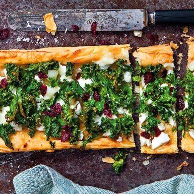 Lyxig pizza som är enkel att göra med färdig smördeg. Bred på crème fraiche och toppa med grönkål, getost och torkade tranbär. Bjud som förrätt eller tilltugg till fördrinken.