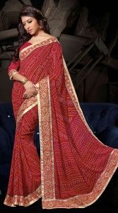 Trendy dark red georgette bandhani print saree which is adorned with rajasthani tie dye chunri printed work all over, zari work in the horizontal panel and lace work on the border. Matching blouse piece attached with this attire. The blouse of this saree can be stitched in the maximum bust size of 40 inches...