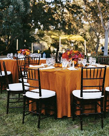 Table settings at Anna and Mason's wedding included orange tablecloths, carrying on the autumnal color scheme.