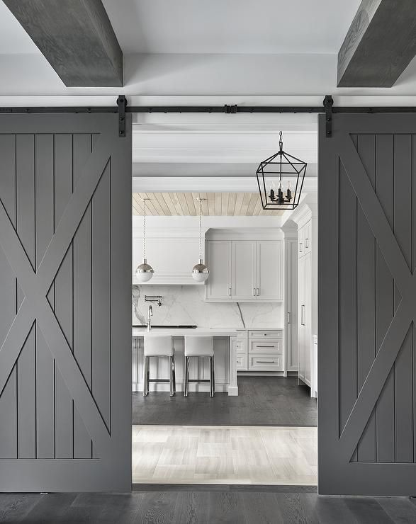 Dual Gray Barn Doors On Rails Open To A Light Gray Kitchen Featuring Light Gray Leather Counter Stools Placed At White Barn Door Interior Barn Doors Barn Door