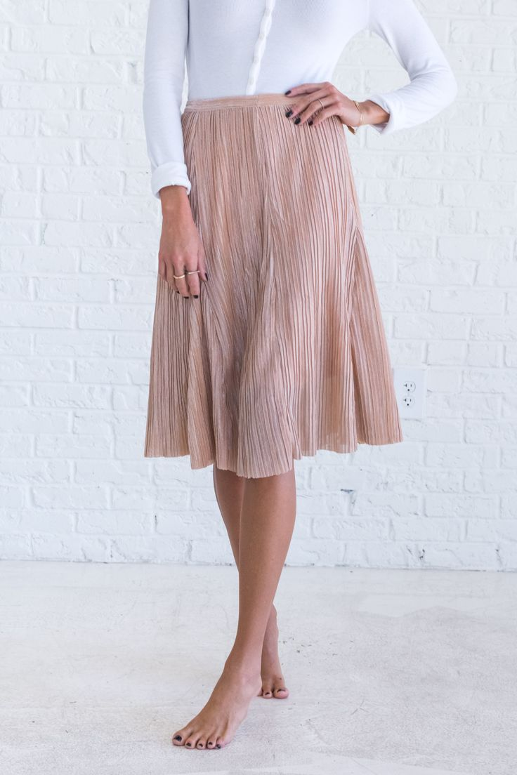 All eyes will be on you with our Dressed Like a Daydream Peach Skirt! This skirt is a pretty peach color with a shimmery top layer. It has subtle pleats and