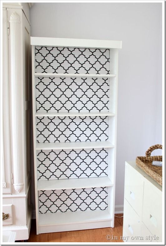 She takes cardboard, cuts it to the size of the back of each shelf, wraps it with her fabric of choice and then puts it back. SO SMART! And easy to change when you got tired of it!