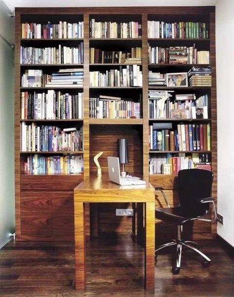 BIBLIOTEKA 12: Regał wraz z biurkiem zrobiono na zamówienie z płyty MDF fornirowanej drewnem orzechowym, pięknie komponującym się z czarnym dębem na podłodze. Zmieściła się tu także kanapa (niewidoczna na zdjęciu) - ponieważ w mieszkaniu nie ma pokoju gościnnego, właśnie na niej sypiają goście.
