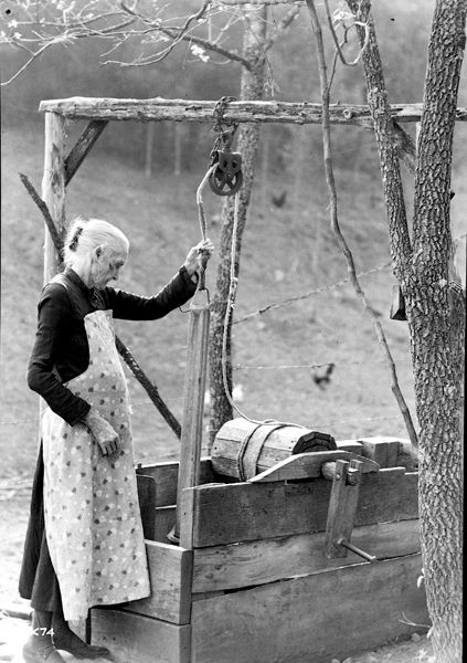 woman drawing water from a well, country life