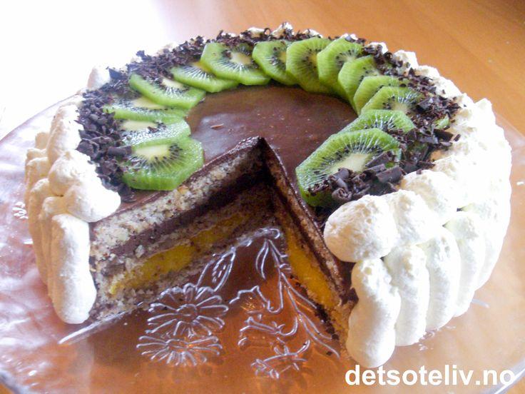 """WOW - for en festkake!!! """"Wienerdronning"""" er en eksklusiv drøm av en kake som består av 3 myke mandelbunner som fylles med et lag eggekrem og et lag sjokoladefromasj. Kaken dekkes med sjokoladefromasj og pyntes med krem, høvlet sjokolade og kiwi. NYDELIG!"""
