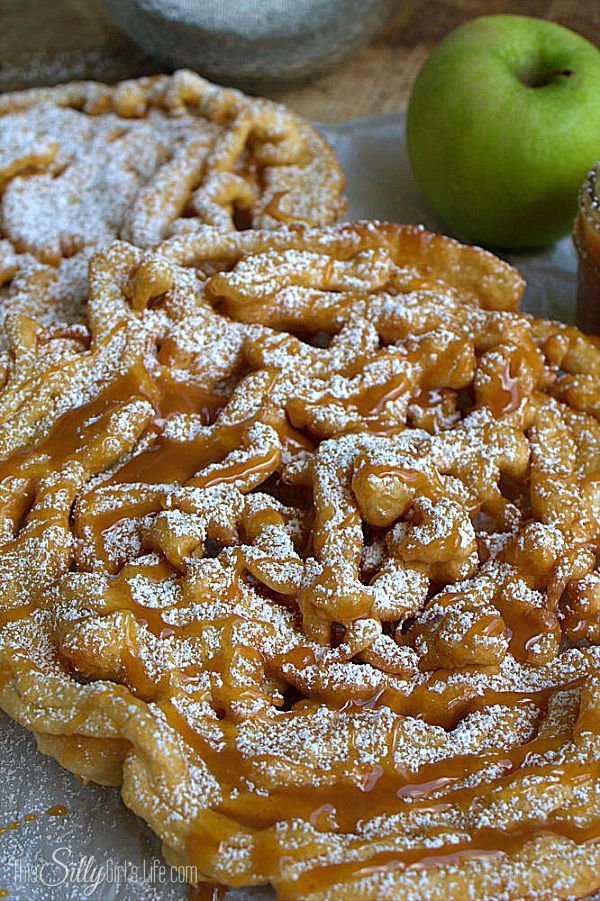 Caramel Apple Funnel Cakes, spiced funnel cake mix loaded with diced apples, dusted with powdered sugar and caramel drizzle!
