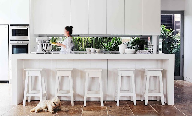 modern white kitchen with lush green outlook to add colour