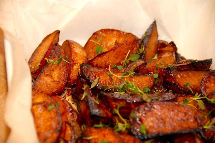 De smager lige så godt som de ser ud, de karamelliserede kartoffelbåde. Kartoflerne er nemme at lave, og du anretter dem med en smule frisk timian. Foto: Guffeliguf.dk.