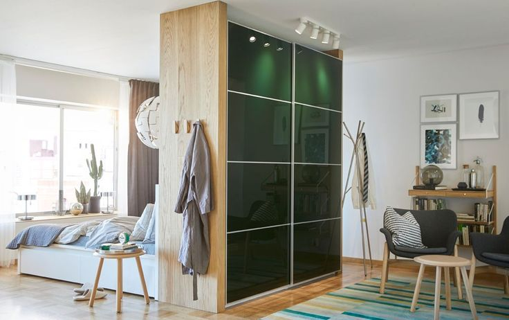 Mørk grønn garderobe med skyvedører brukt som romavdeler mellom et soverom og ei stue.