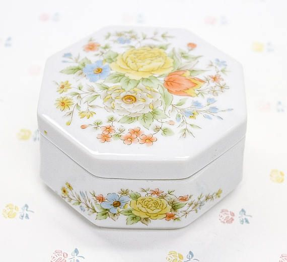 A white porcelain jewelry/trinket box in the shape of an octagon, with a multi-colored floral design on the lid and on the sides of the container base. JAPAN is marked on the bottom, and the original gift label that reads Klassen Giftware Condition: Item is in excellent vintage