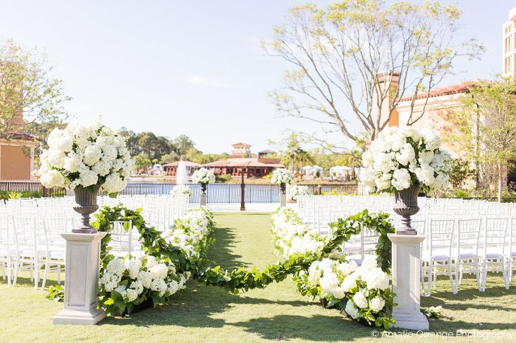 traditional and elegant outdoor ceremony featured large and lush urns filled with white hydrangea and white stock at the entry and top of the aisle.  the aisle was lined with a full hedgerow of white hydrangea and roped off with a gorgeous garland of greenery.