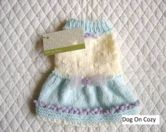 An ideal little Cape sweater for warmer days or for wear indoors. Trimmed with little ruffles on the bottom. Pretty Posie with button trim. Nice little sweater cape to wear alone or over other clothing for any little sweetie to dress up!!! Easy to put on. Has front leg straps on the inside so Cape does not twist around to the front, but says in place when wearing. Knit in a soft Lime Green with Peach trim and Posie.  This Sweater Cape is made for smaller dogs - is available in sizes XXSMALL…