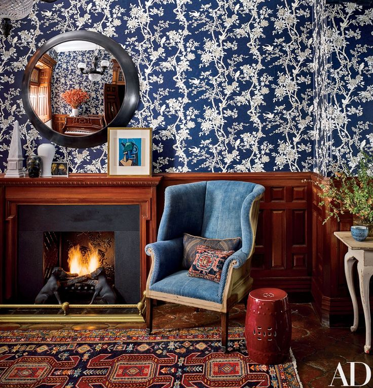 Inside Jessica Chastain's New York City Apartment by Jesse Carrier and Mara Miller | In the foyer, the chambray wing chair and floral wallpaper are by Ralph Lauren Home. The McLain Wiesand mirror is from John Rosselli & Assoc., and the Azerbaijani rug is vintage | Blue, white, wood, red accents.