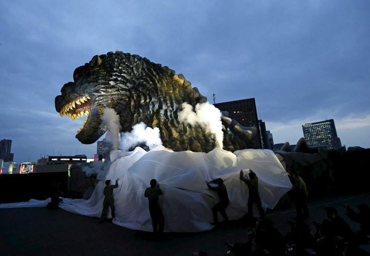 A real-scale head of Godzilla is unveiled at the balcony of a newly-built commercial complex as a new Tokyo landmark at Kabukicho shopping and amusement district in Tokyo