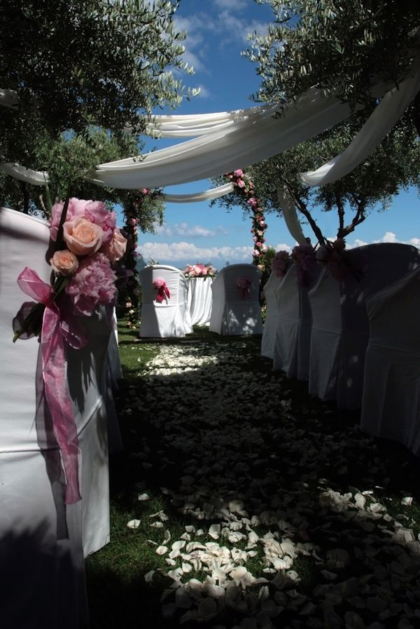 beautiful outdoor ceremony aisle decor - white silk draped from trees over the aisle covered with white rose petals and white seat covers with pink and peach floral decor - photo by Italian wedding photographer JoAnne Dunn