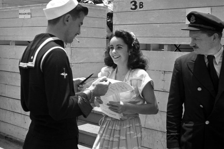 Not originally published in LIFE. In 1945, at age 13 and already a veteran of five films, Elizabeth Taylor signs autographs during a charity cricket match at Los Angeles' Gilmore Stadium.