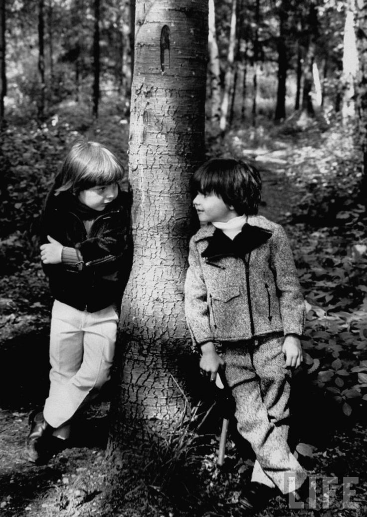 Two little boys standing against both sides of the tree modeling thick winter jackets and a warm pant set . Paris . June 1967 . Photo by Pierre Boulat