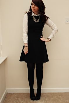 white button up blouse layered under a black dress