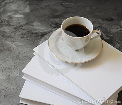 A cup of coffee and some books on marble background