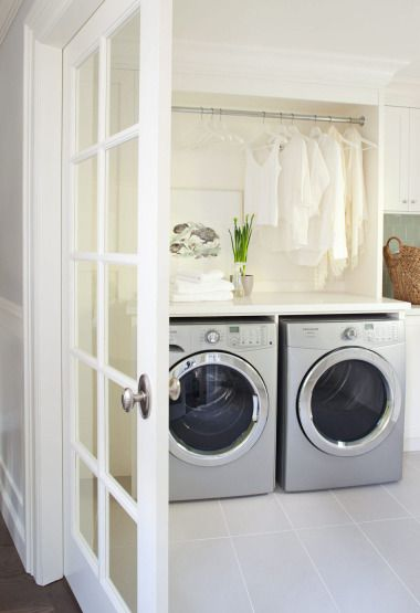 Huge laundry room design with silver front-load washer and dryer, white shaker cabinets with white quartz countertops, French doors and green glass subway tiles backsplash.