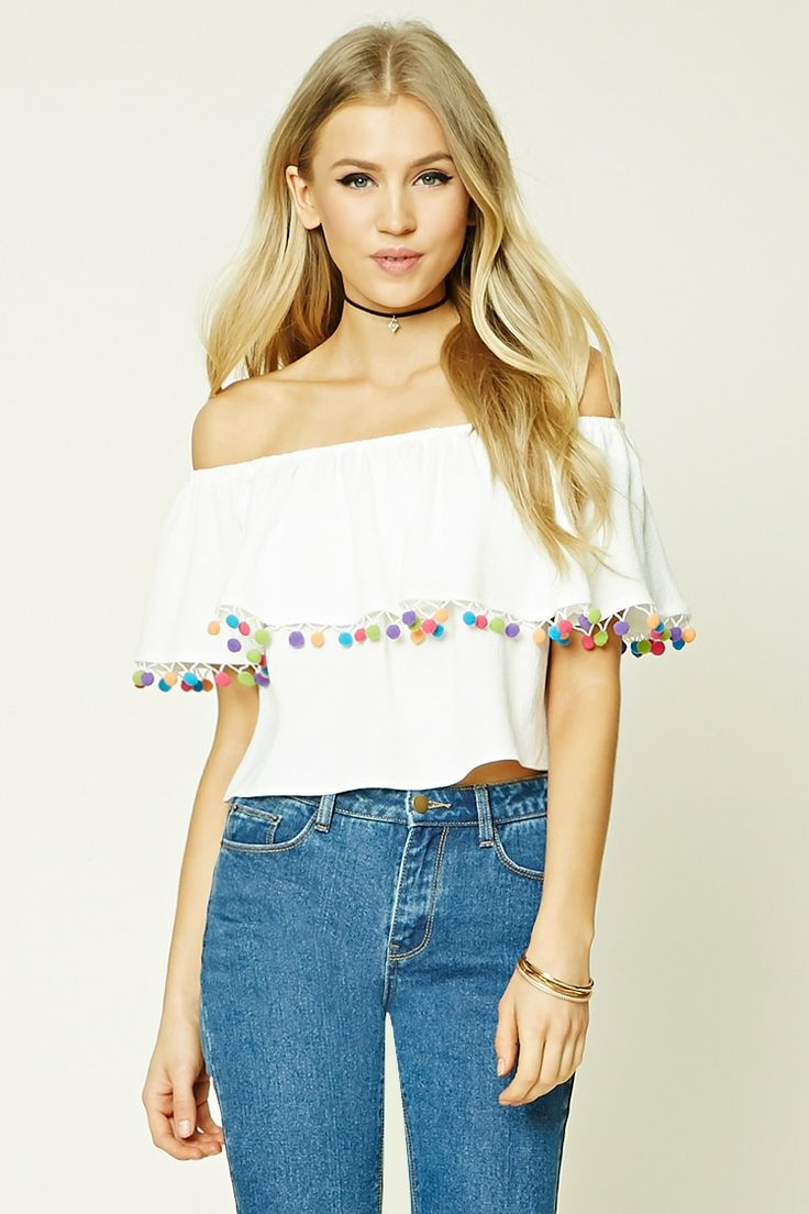 A woven top featuring an off-the-shoulder design, pom pom trim, short sleeves, an elasticized neckline, and a cropped and billowy silhouette.