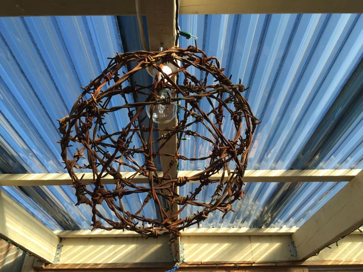 A light fitting inside some old rustic fencing wire made into a ball. Great for a outside area.