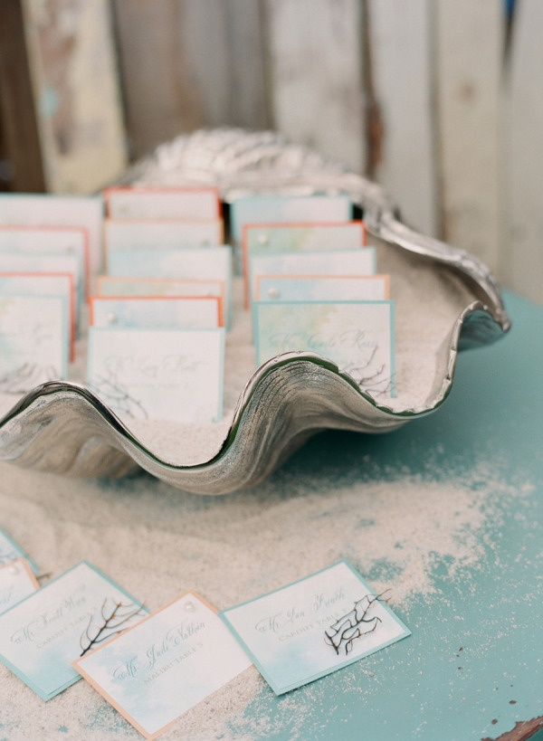 Sand and shell escort card display with teal and coral cards. (@Ashley Perry) Photography by kissthegroom.com