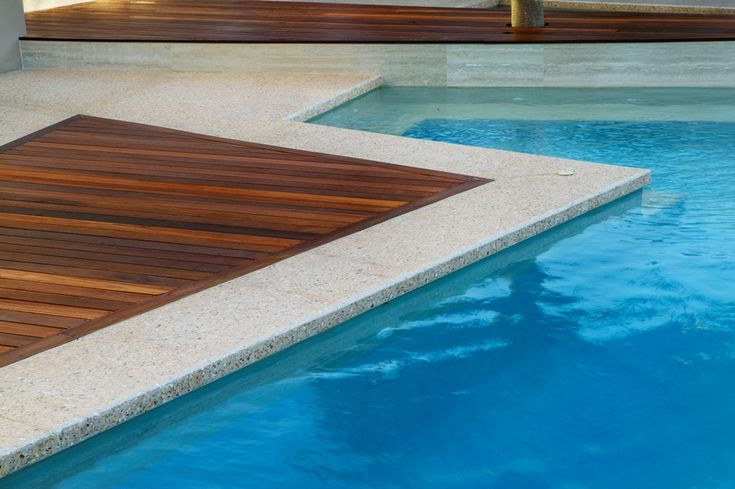 Perfect your pool area with an exposed aggregate concrete and timber combo!