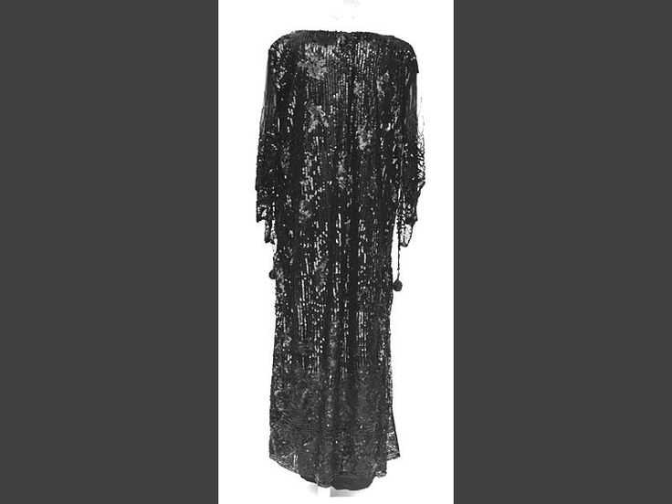 MMT 000293 :: klänning Klänning av svart atlassiden med överklänning vars kjol är slitsad i höger sida och som är av svart tyll helt överbroderad med svarta dels släta, dels rutade paljetter. Ärm-vinge av svart paljett- och pärlbroderad tyll som baktill är avslutad med en hängande pärklädd boll.
