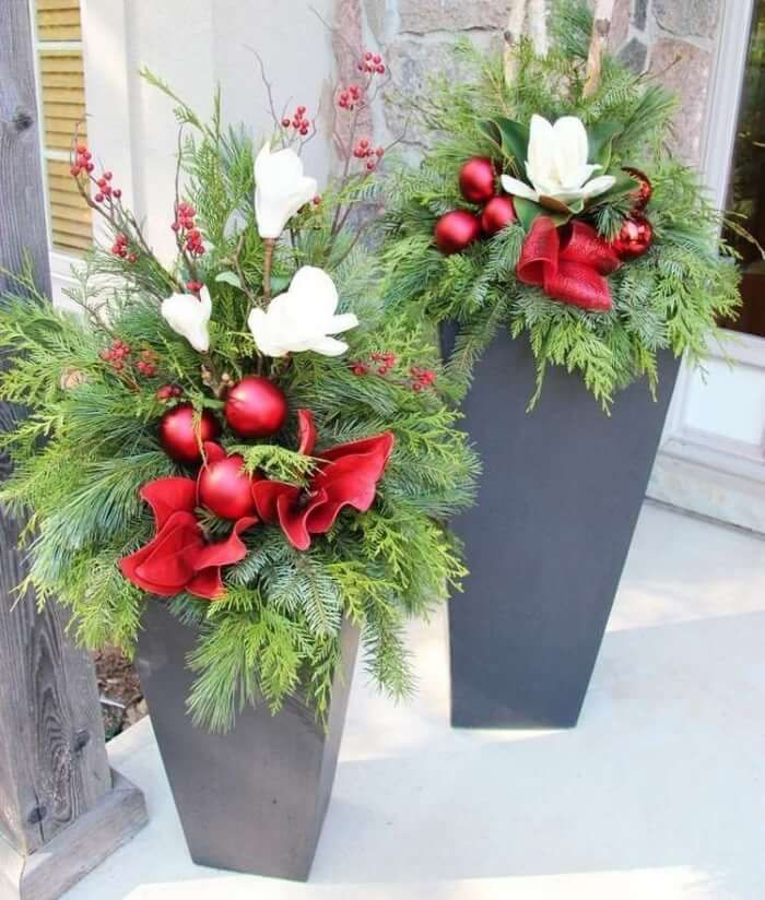 compositions de branches de conifères, boules de Noël rouges, baies rouges et fleurs blanches en jardinières métalliques