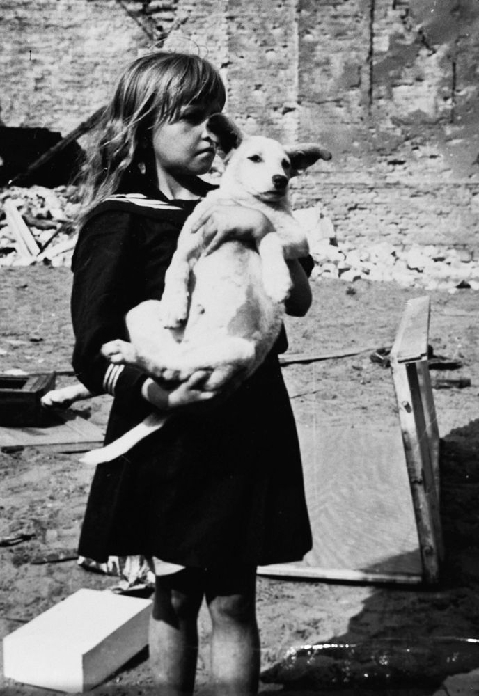 A girl holding her dog in a devastated neighborhood in Warsaw, Poland, 5 Sep 1939.