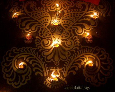 An 'alpona' embellished with diyas (earthen lights). Alponas are colorful motifs painted with rice flour on certain religious festivals or weddings.