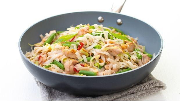 Rýžové nudle s kuřecím masem a zeleninou: Nudle dejte do mísy a zalijte je vroucí vodou. Přiklopené nechte 6–8 minut stát, aby změkly. Sceďte je a dejte stranou. Olej rozpalte ve wok pánvi, přidejte kuřecí kousky a opékejte je 2–3 minuty. Přidejte česnek, fazolky a chilli papričku a za občasného míchání opékejte další 2 minuty. Nakonec přidejte zelí, obě omáčky a nudle a společně 1 minutu prohřejte. Posypte arašídy a jarní cibulkou a podávejte.