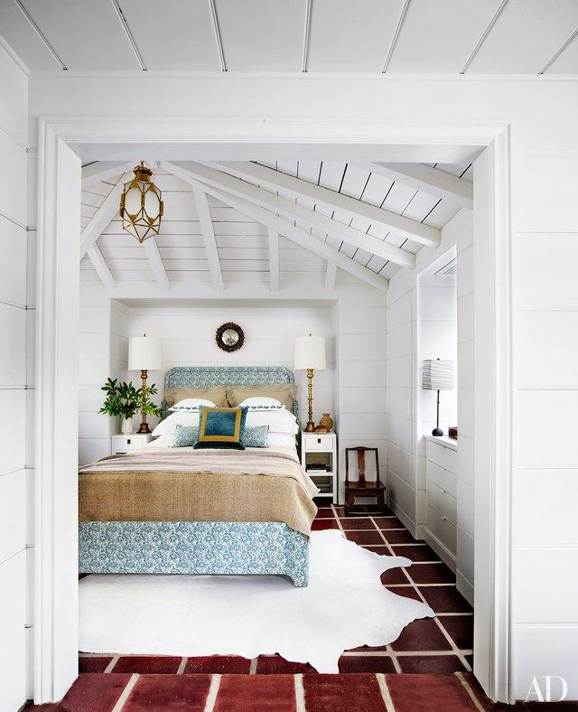 In the master bedroom, a vintage brass lantern and an Onik Agaronyan mirror, both from Downtown, hang above a custom-made bed upholstered in a Fortuny print | archdigest.com