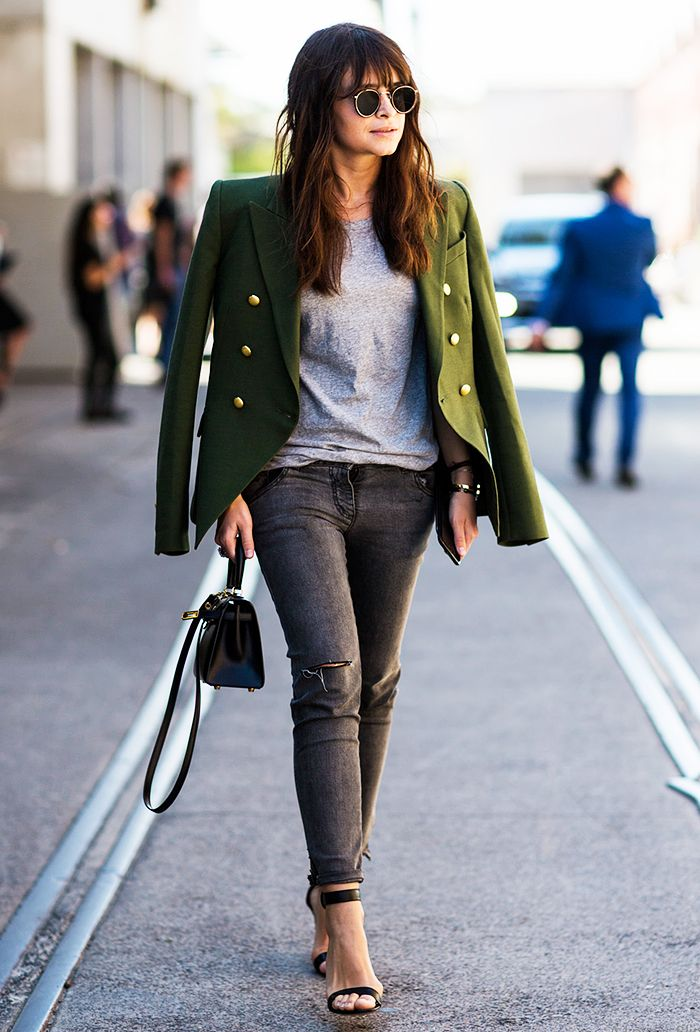 Miroslava Duma in a grey t-shirt, black heels, a green jacket, and round sunglasses