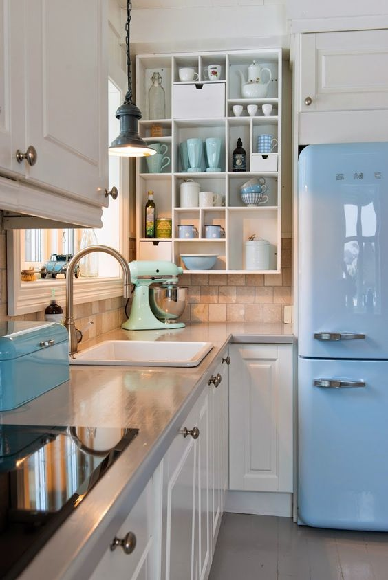 Retro kitchen design idea with great combination of blue fridge and white kitchen