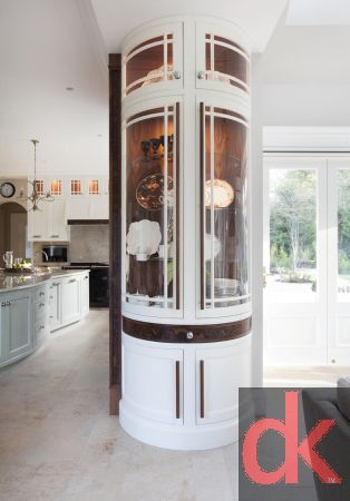 Luxury hand painted kitchen cabinetry with walnut kitchen cabinetry doors with burr walnut accents.  Curved glass kitchen doors with custom inlay.  Exotic stone worktops along with custom made dining table and chairs.  Curved Glass Display Unit