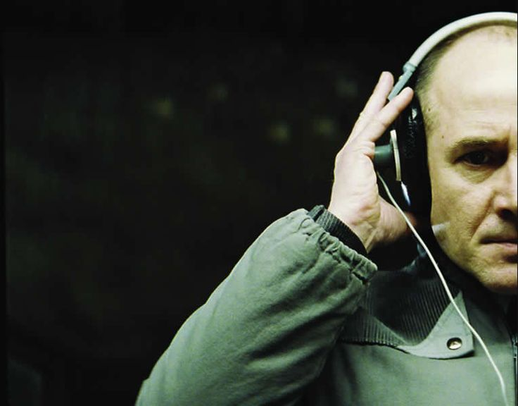 Still from the film, showing Captain Wiesler listening intently to headphones