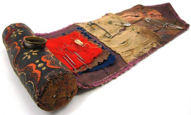 "A ""soldier's housewife"" sewing kit made of cloth that has been lacquered black and stenciled with floral design. The kit was used by Private Marcus Daniels during the Civil War. The kit rolls closed around a cylindrical pin cushion containing a tinned iron thimble with a brass rim. The interior of the kit has three wool flaps of sewing needles and two fabric patches of safety pins.  Minnesota Historical Society"