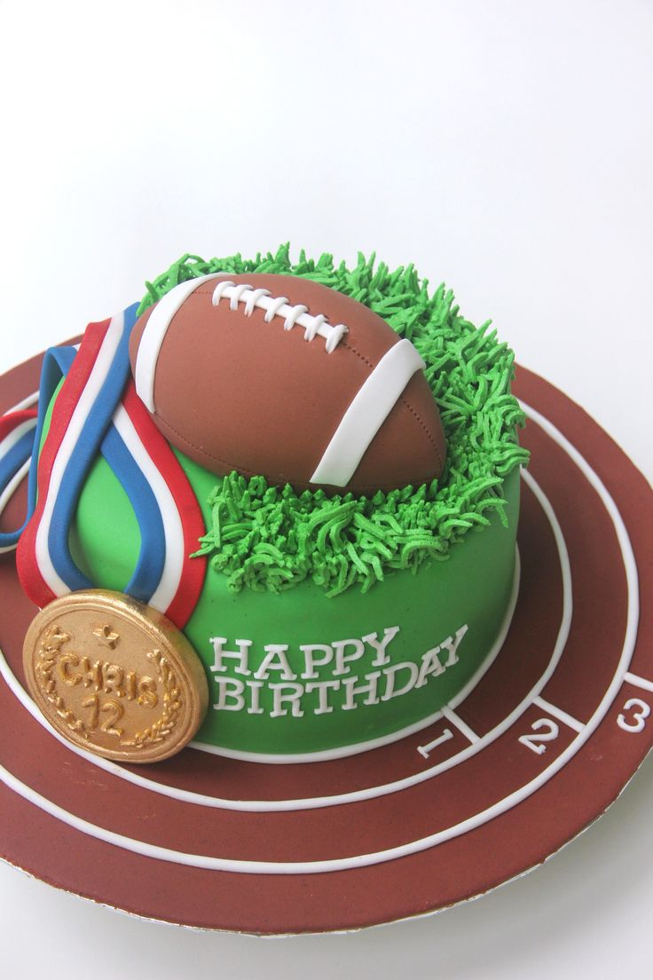 Sports-themed cake with American Football and Gold Medal toppers, and piped buttercream grass by Butter Home Bakery