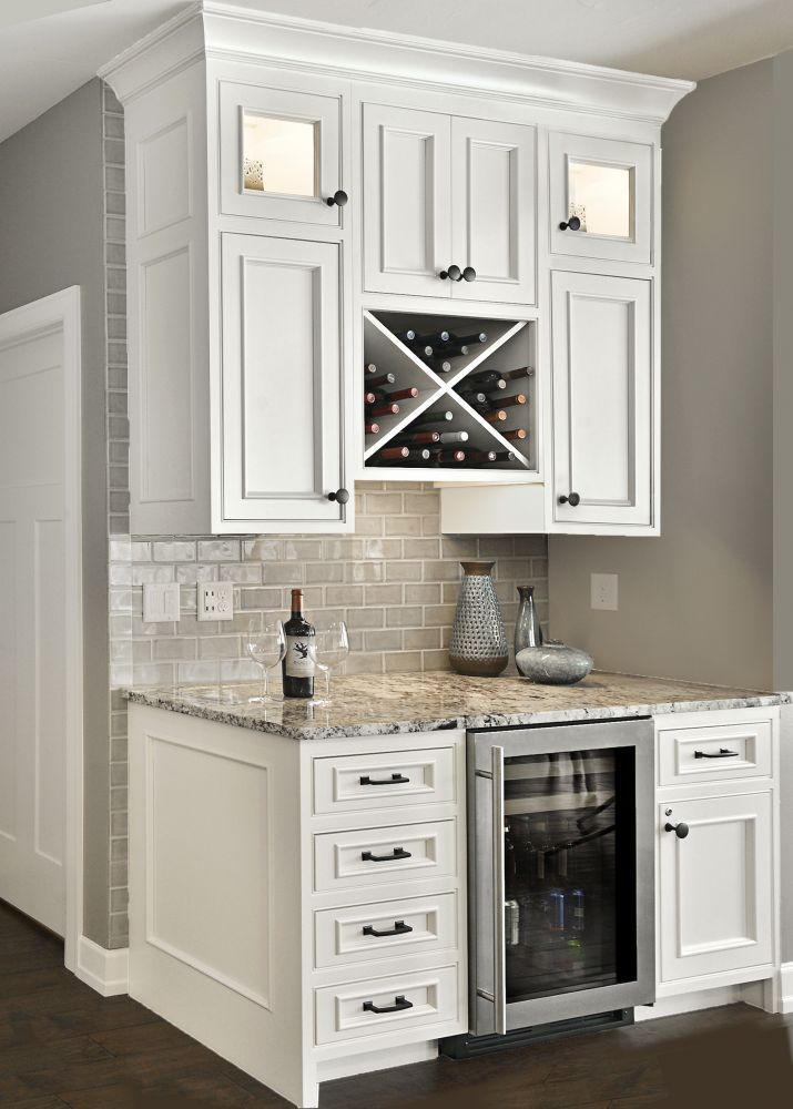 """Custom beverage center with """"X"""" wine rack and small refrigerator. Notice the beaded face frames, inset doors and panelized ends."""