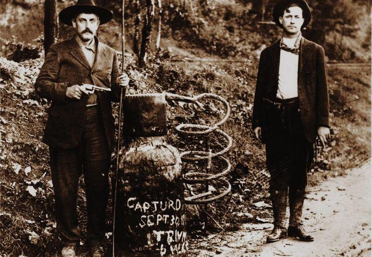 Law enforcement officers stand beside a captured moonshine still